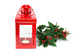 Red lantern with tealight holly twigs and berries