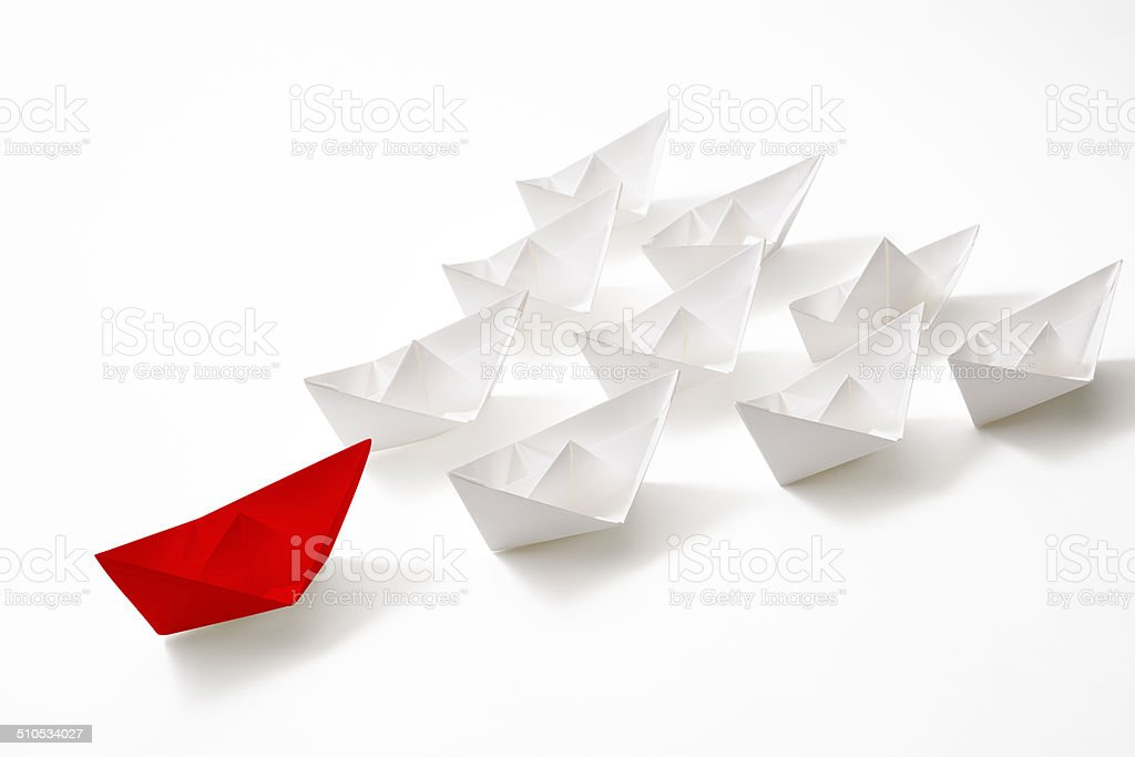 Red leadership paper boat of convoy on white background stock photo