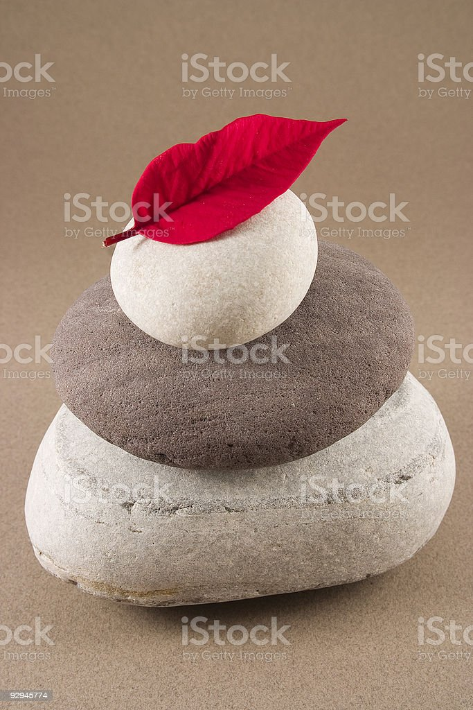 Red leaf on the top of 3 balancing pebbles stock photo