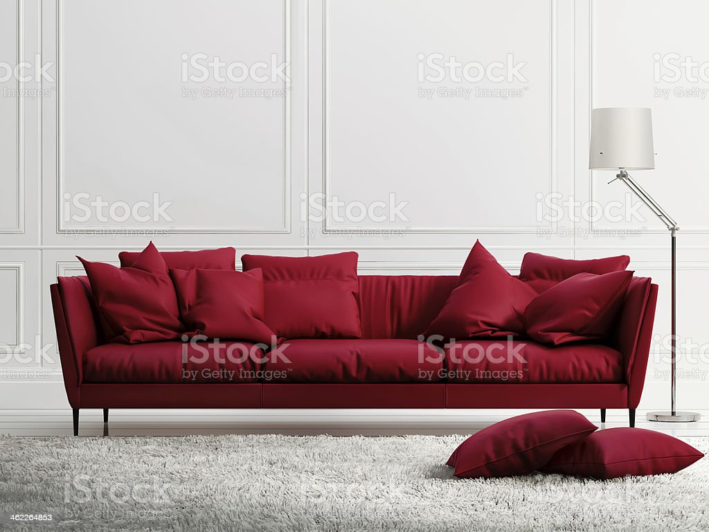 Red leather couch in a room with white walls stock photo