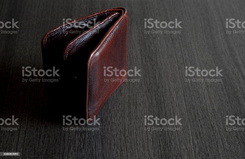 Red leather wallet on wooden table stock photo