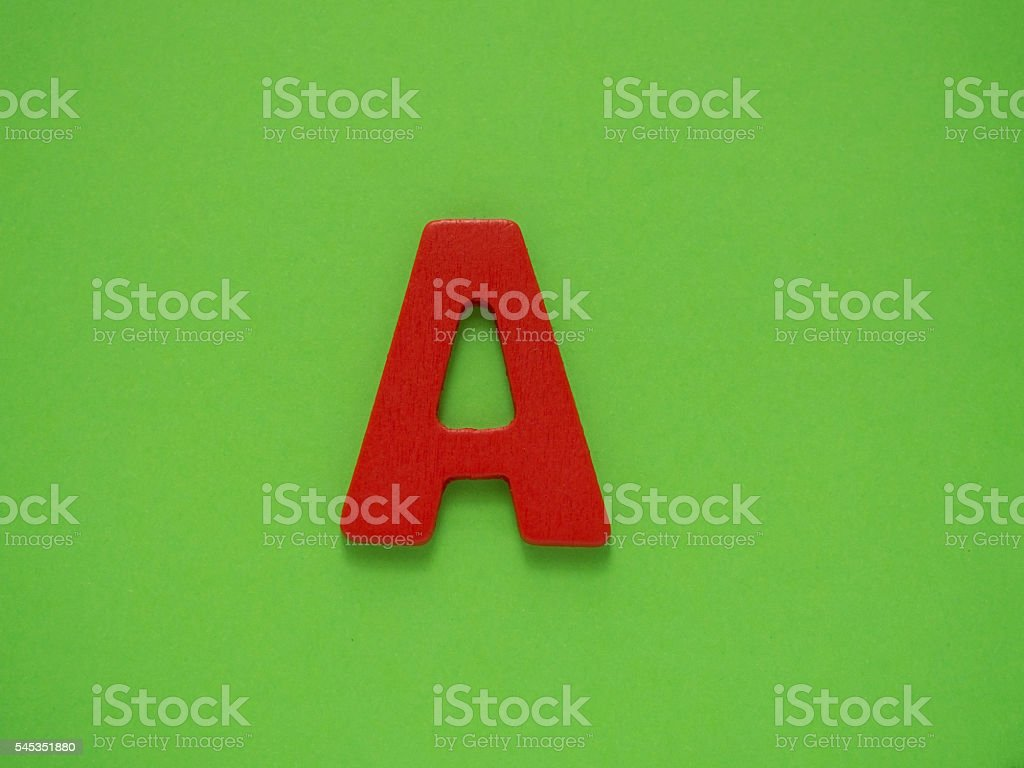 Red letter A from wood on green background. Alphabet. stock photo
