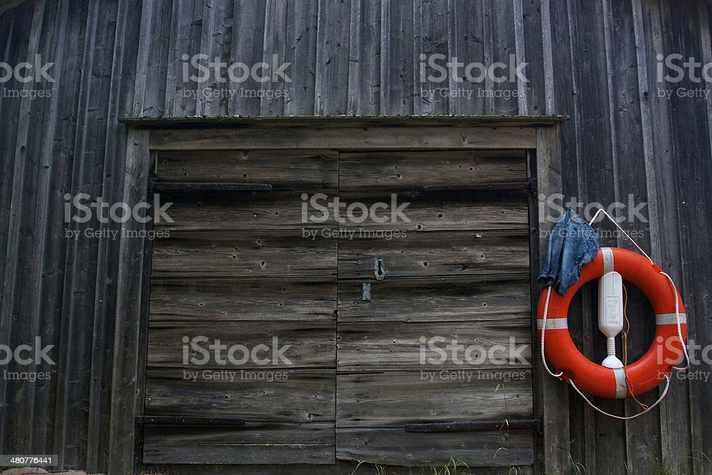 Red life ring hanging on old wooden garage stock photo