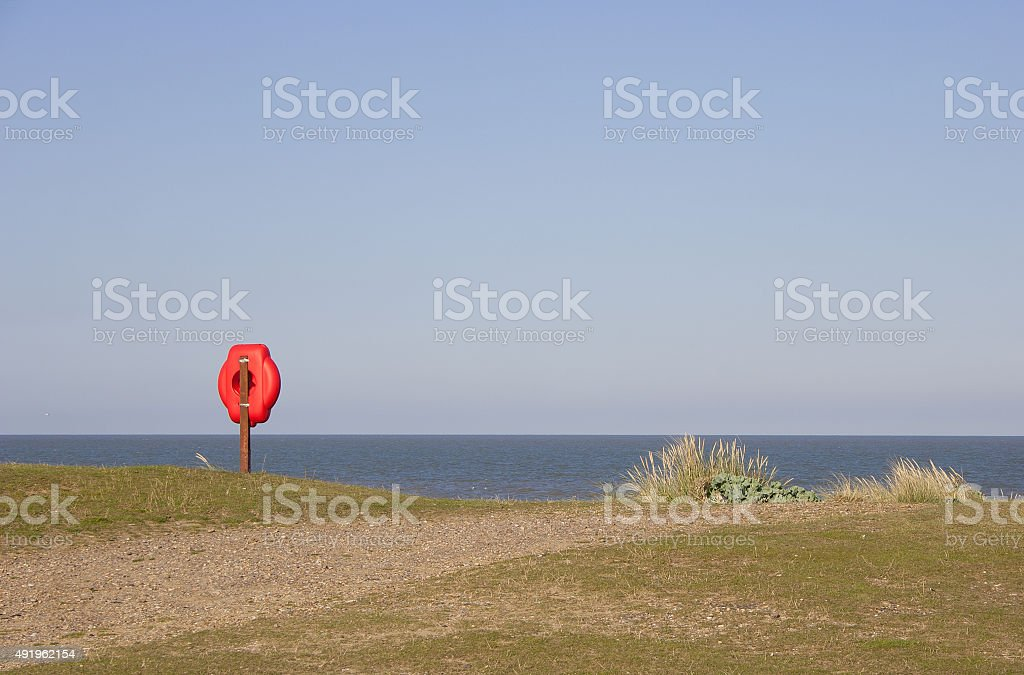 Red lifebelt post against clear blue sky, Sizewell, Suffolk stock photo