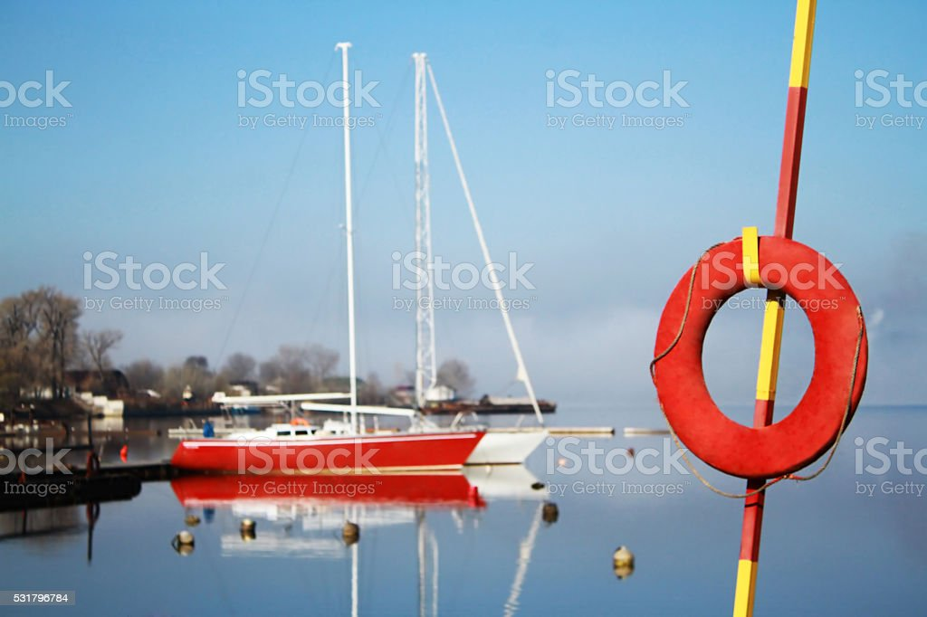 Red lifebuoy on a background of two yachts stock photo