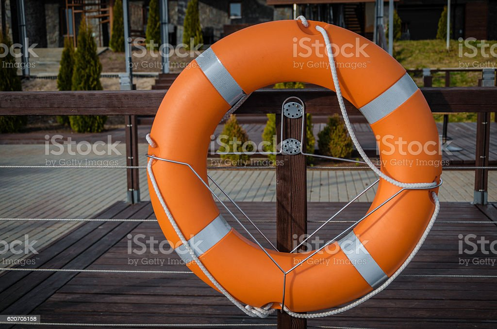 Red lifebuoy with rope  in port stock photo