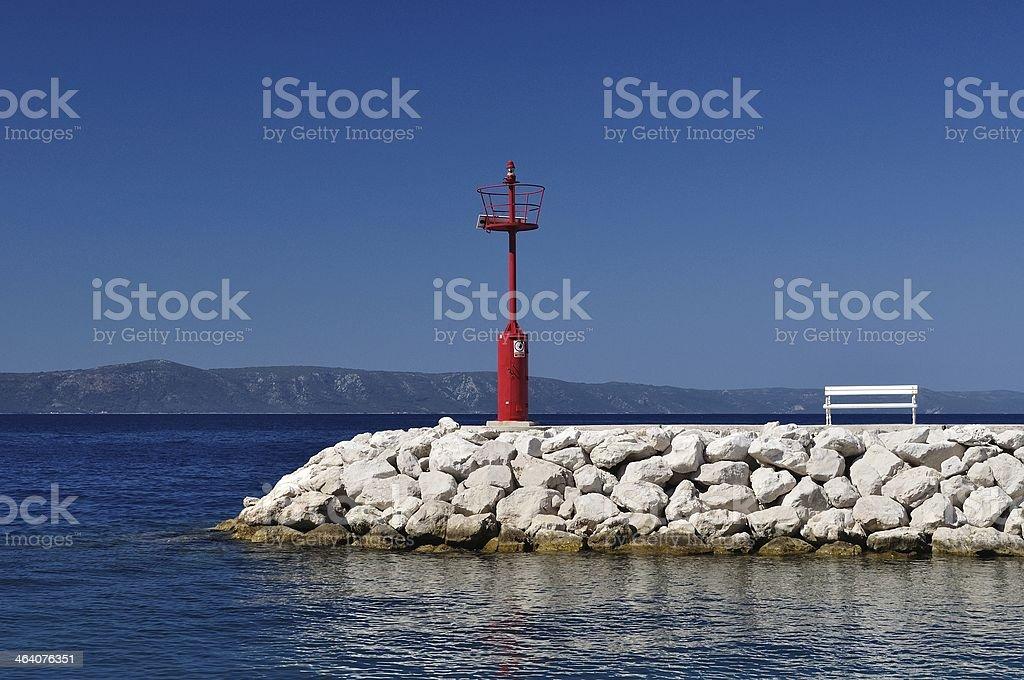 Czerwona Latarnia morska w porcie z kamieni i biała Ławka zbiór zdjęć royalty-free