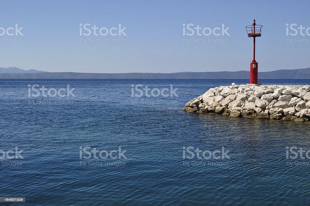 Czerwona Latarnia morska w porcie z kamieni zbiór zdjęć royalty-free