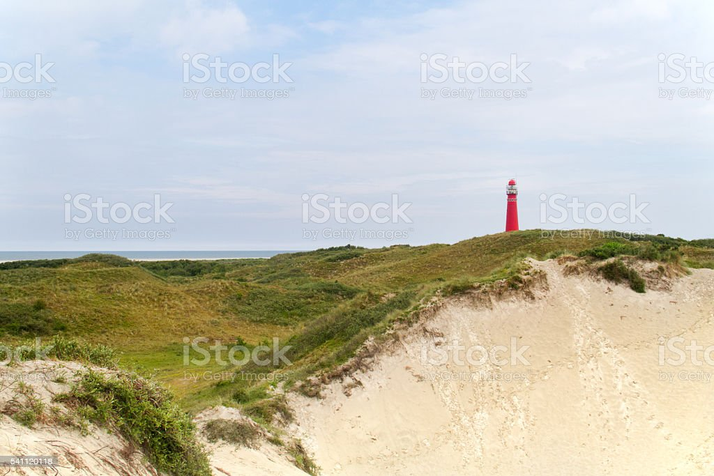 Red lighthouse in the dunes stock photo