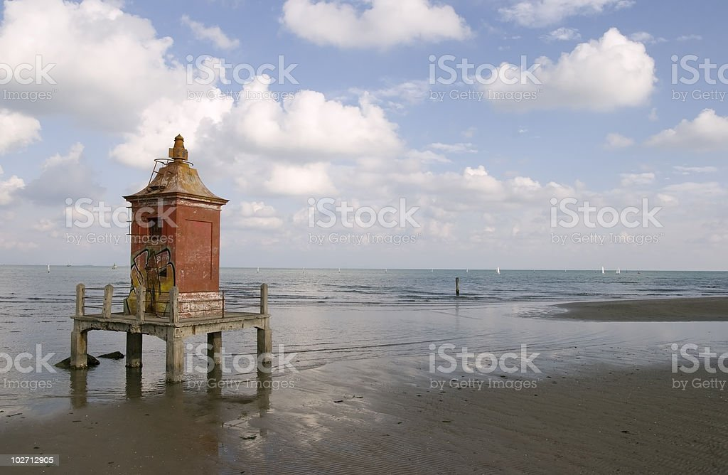 Red lighthouse on the sea stock photo