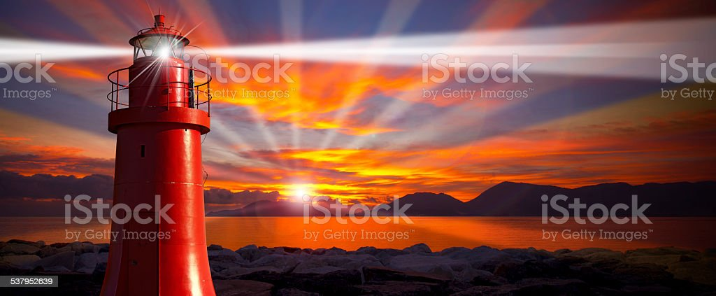 Red Lighthouse with Light Beam at Sunset stock photo
