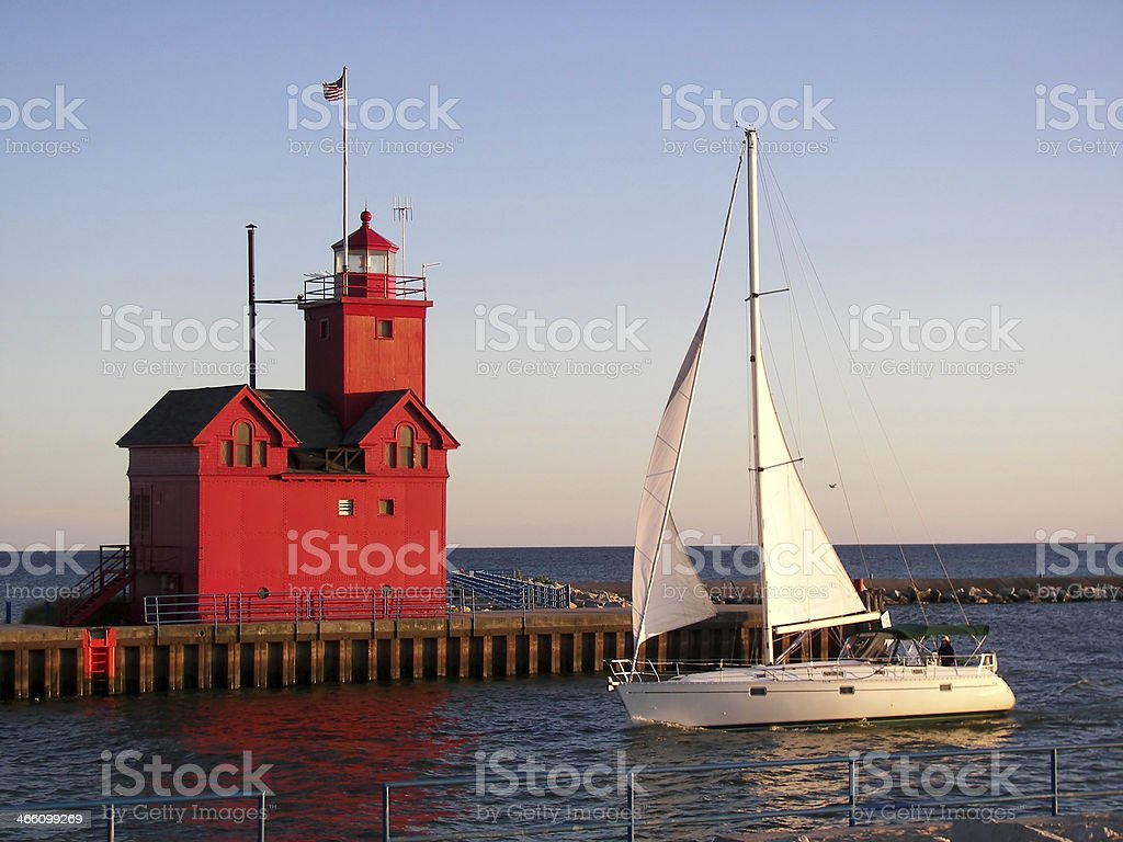 red lighthouse with sailboat stock photo