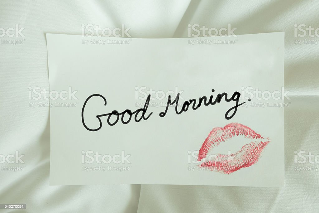 Red lips kiss Good morning on white note message on bed stock photo