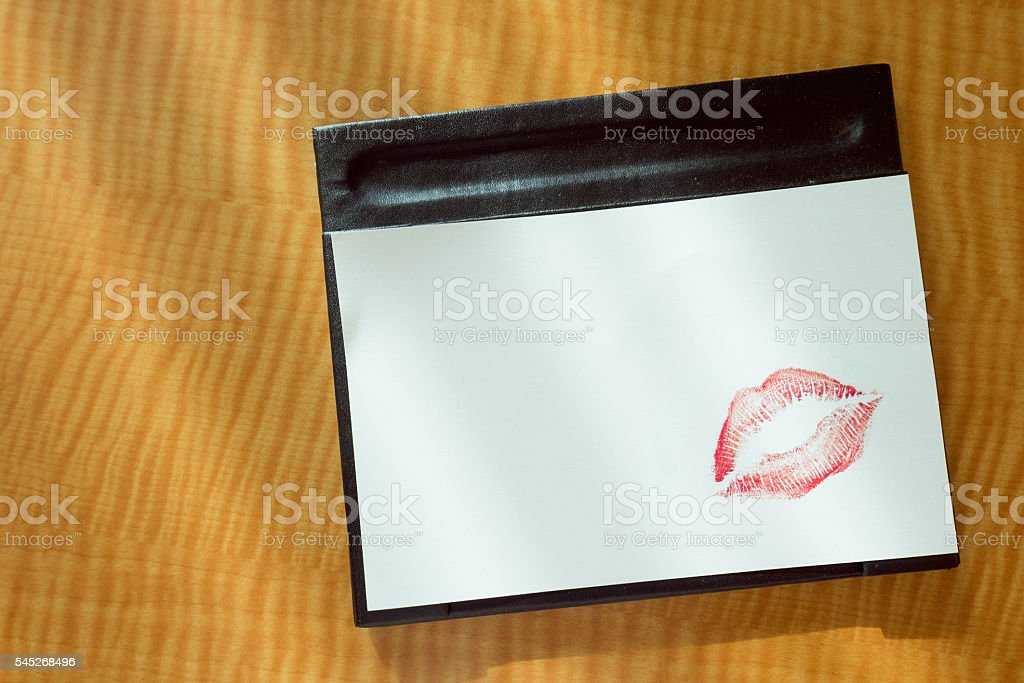 Red lips kiss on white note message on table stock photo