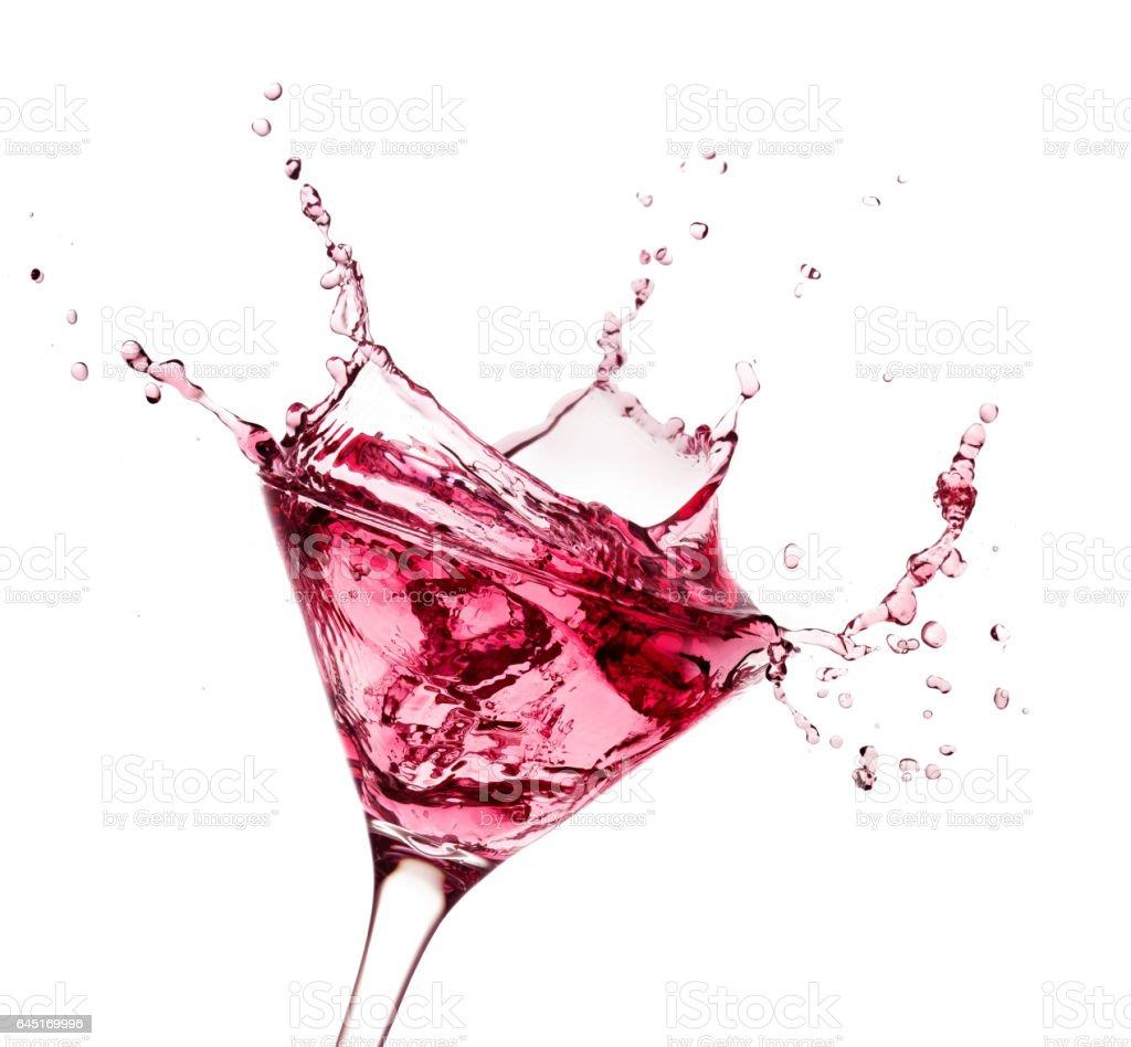 red liquid splashing in martini glass isolated on white stock photo