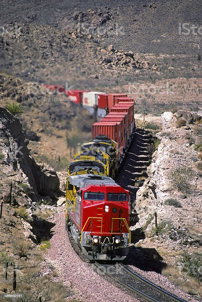 Red loco and container train in rugged canyon stock photo