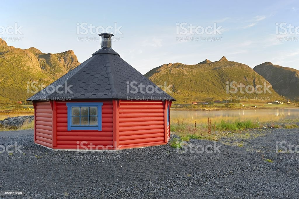 Red log cabin in background of fjord and mountains royalty-free stock photo