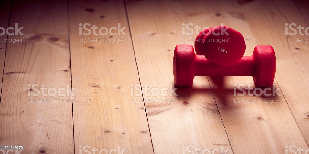 Red loght dumbbells on a wooden flor stock photo