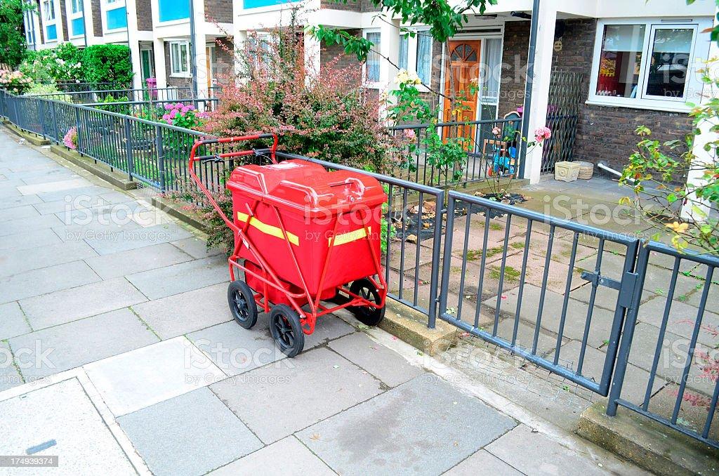 red mail buggy on sidewalk in London neighborhood stock photo
