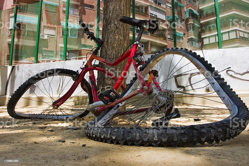 Red mangled bike propped against a tree on the street royalty-free stock photo