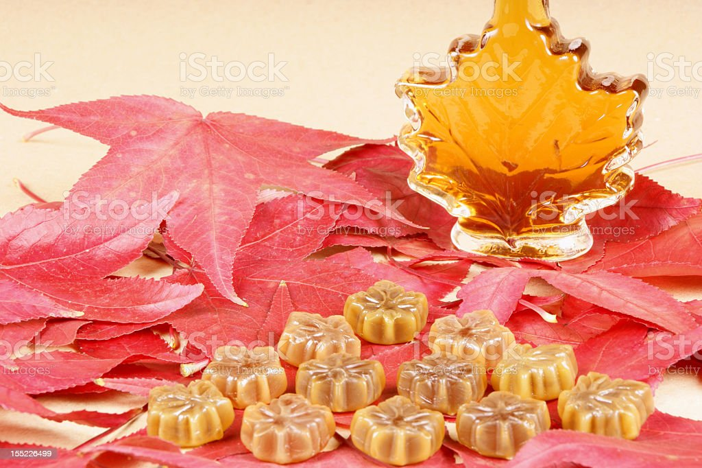 Red maple leafs with maple syrup and maple candy stock photo