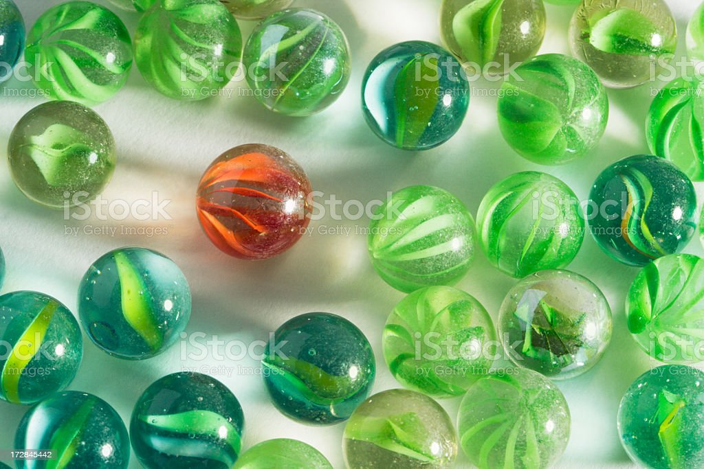 Red Marble Standing Out from the Crowd of Green Individuals stock photo