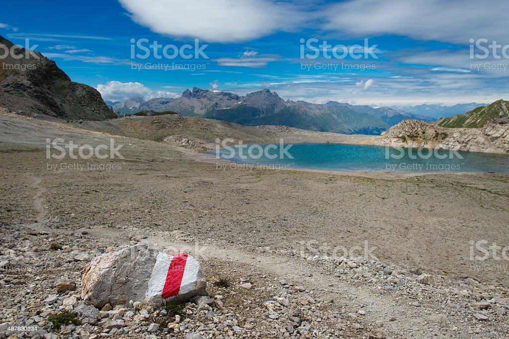 Red mark on stone toward a mountain lake stock photo