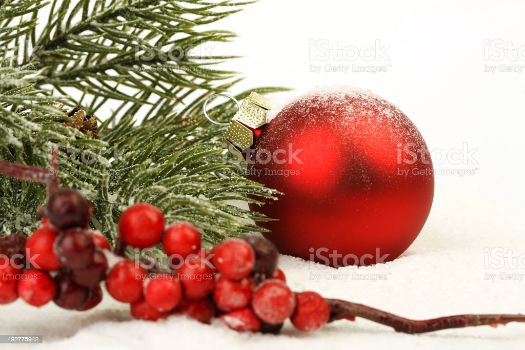 Red matt christmas ball on snow and red rowanberries stock photo