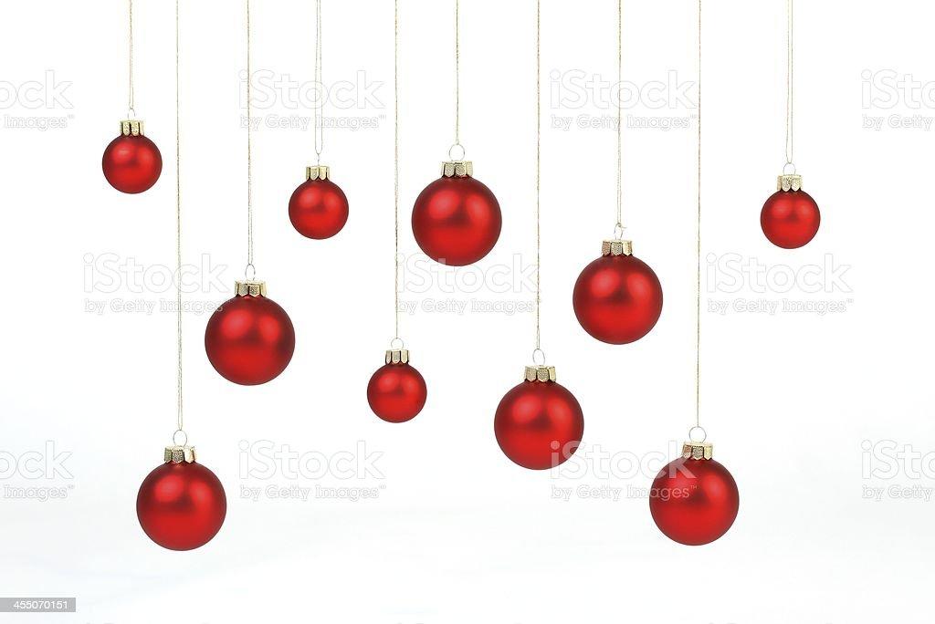 Red matt christmas balls hanging on golden strings stock photo