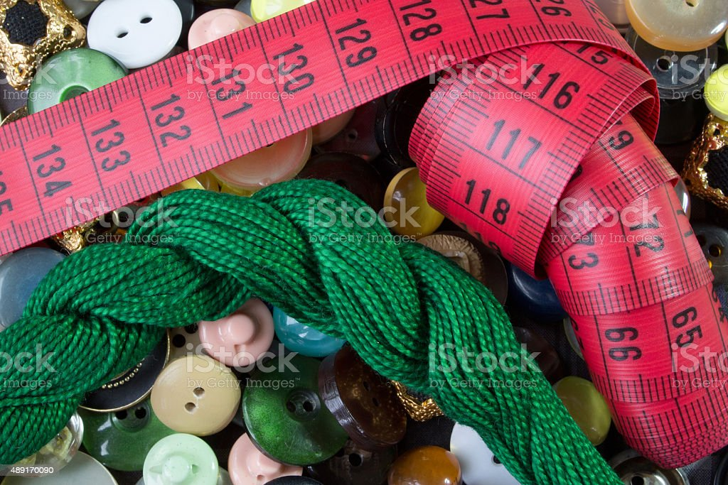 red measure and green thread on old fashioned buttons background stock photo