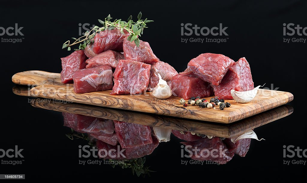 Red meat on wooden board, against black background stock photo
