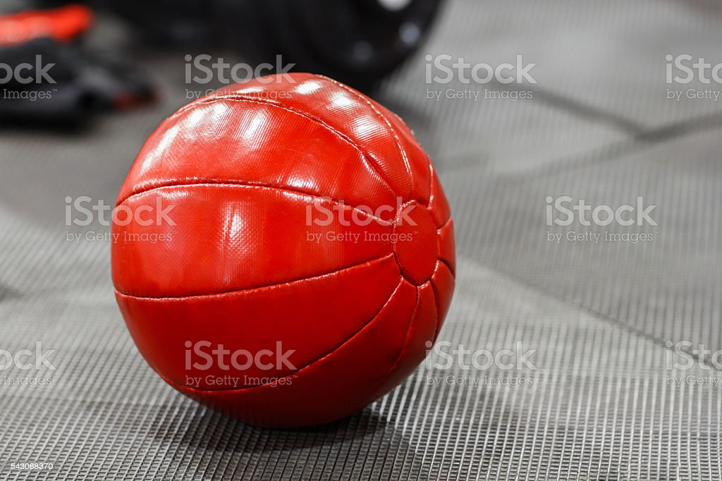 Red medicine weight ball on gym floor closeup stock photo