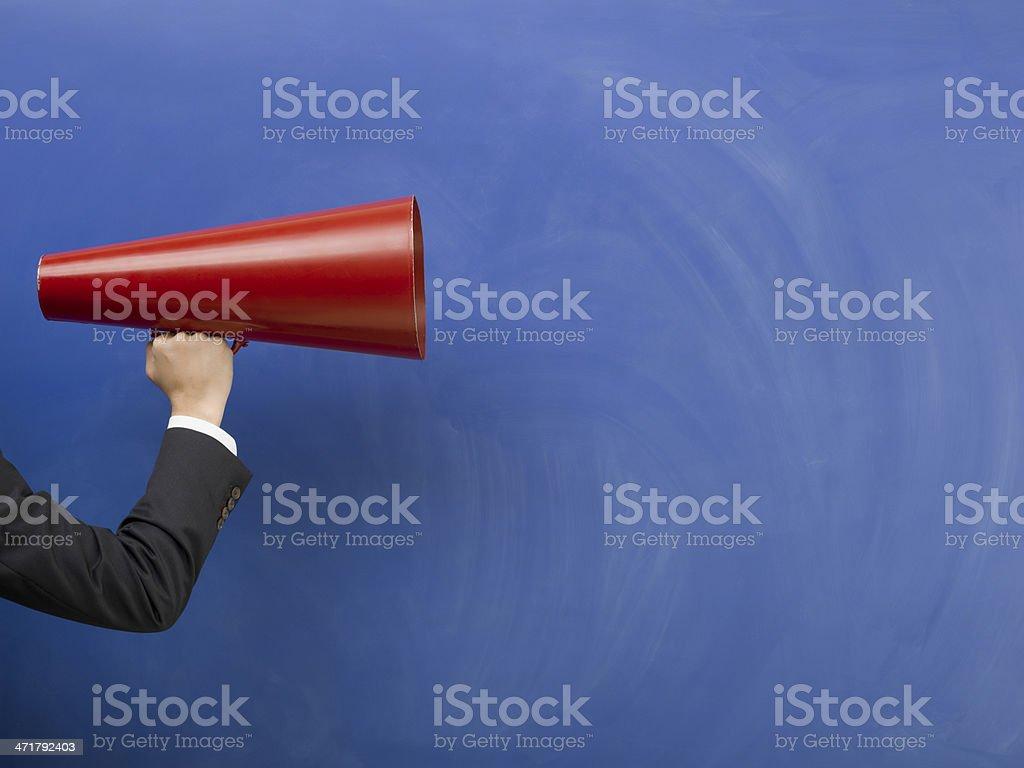 Red megaphone in human hand on blue blank blackboard stock photo