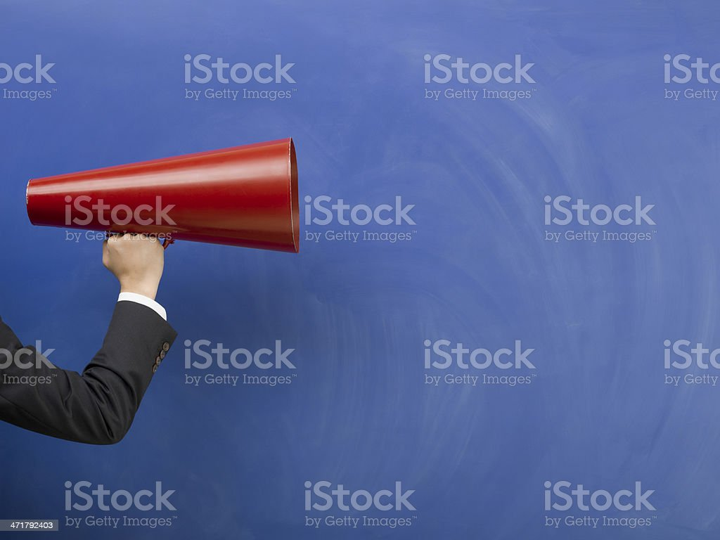 Red megaphone in human hand on blue blank blackboard stock photo