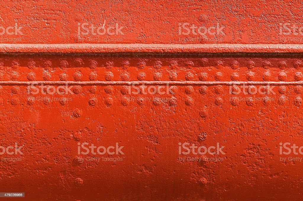 Red metal wall texture with seams and rivets stock photo