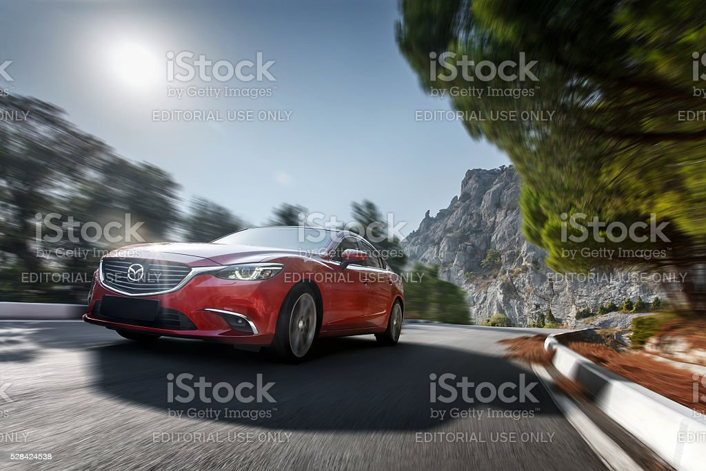 Red modern car drive on asphalt road at daytime stock photo