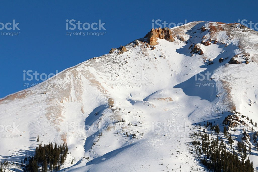 Red mountain covered in deep snow against blue sky stock photo