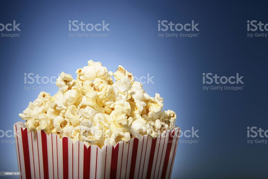 red movie popcorn box with blue background stock photo