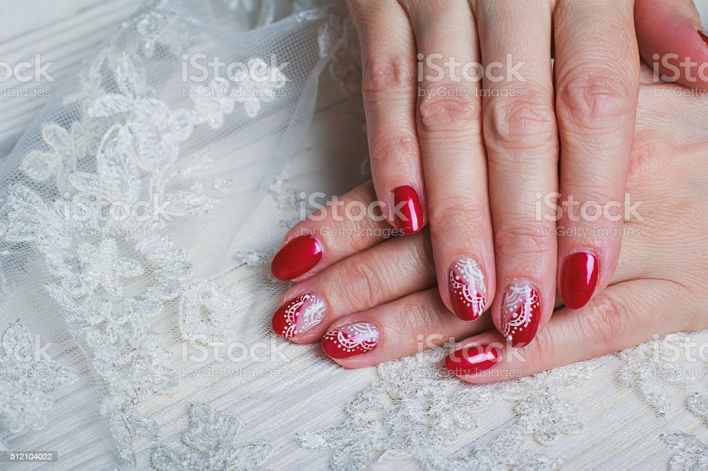 Red nail art with white lace with dots and lines stock photo