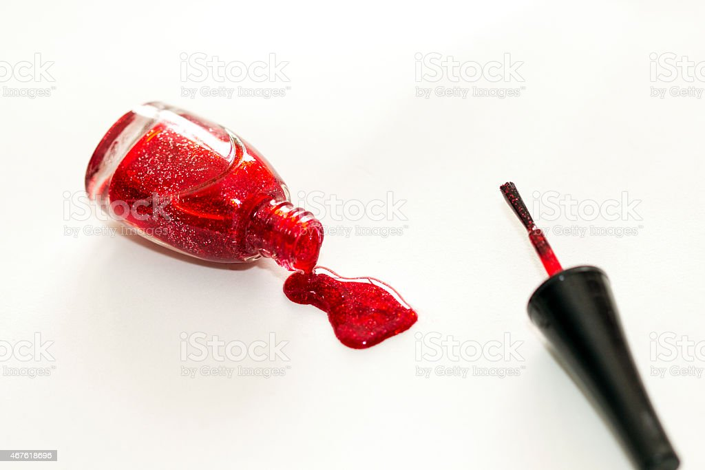 Red nail polish bottle dripping on isolated on white. stock photo