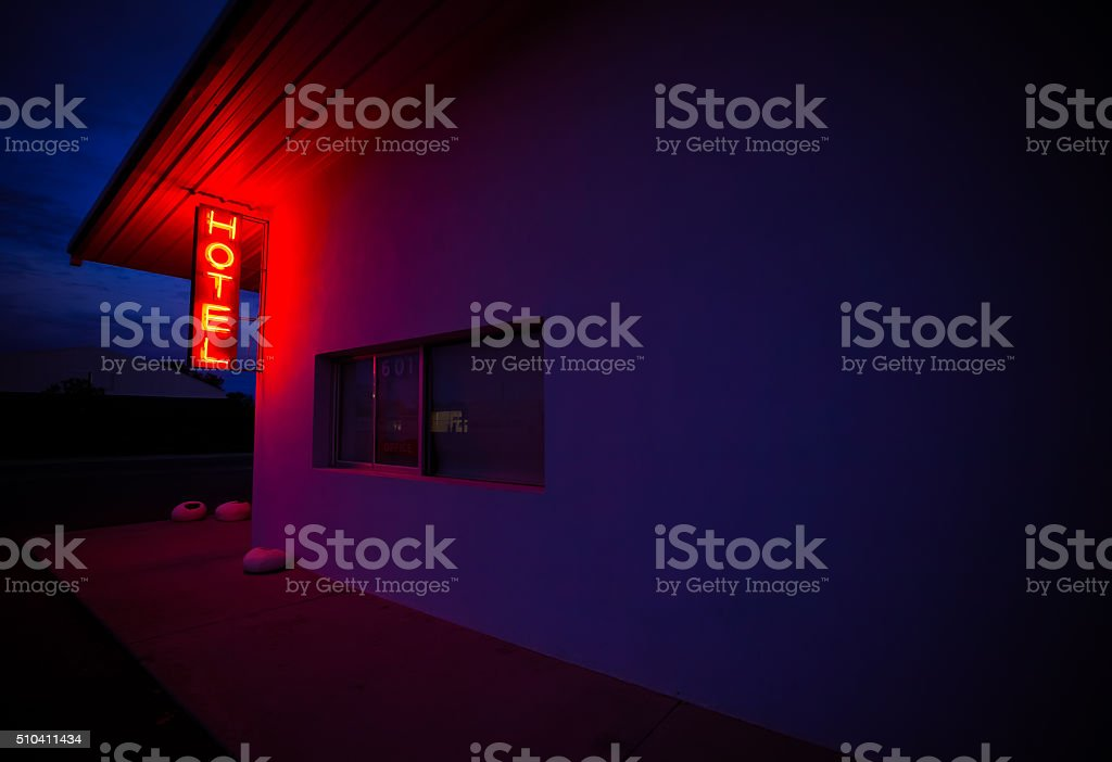 Red Neon Hotel Sign at Dusk in a Small Town stock photo