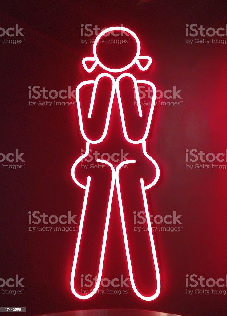 Красный неоновый Знак для девочка, сидящая перед туалетов Стоковые фото Стоковая фотография