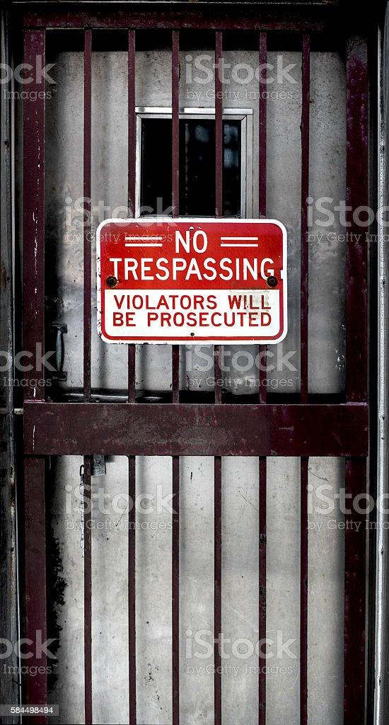 red no trespassing sign on dark bar door stock photo