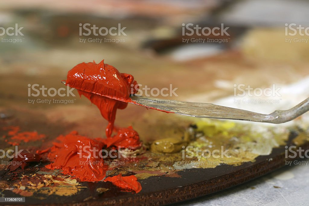 Red oil color on a palette knife royalty-free stock photo