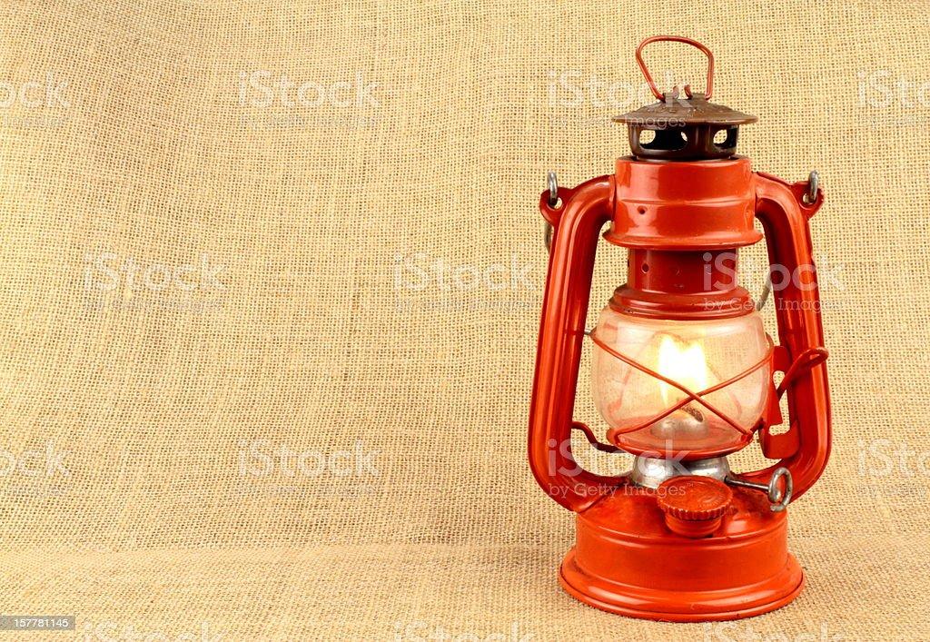 Red oil lamp on burlap stock photo