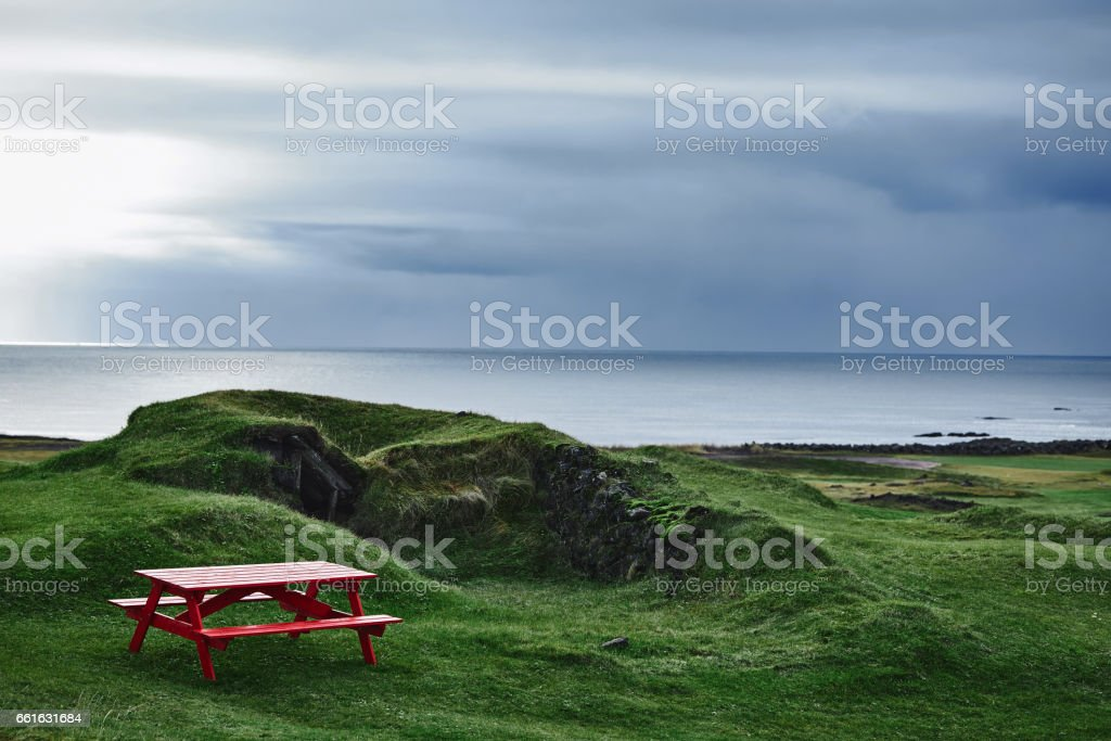 Red old homemade wooden bench on green grass stock photo