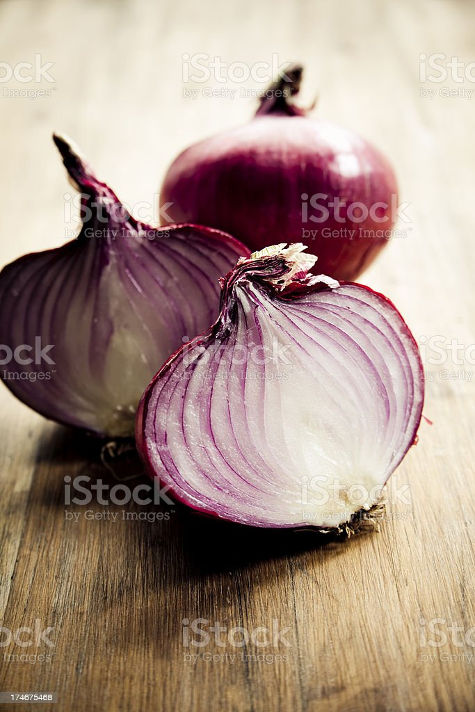 Red onion sliced into half on a wooden table stock photo