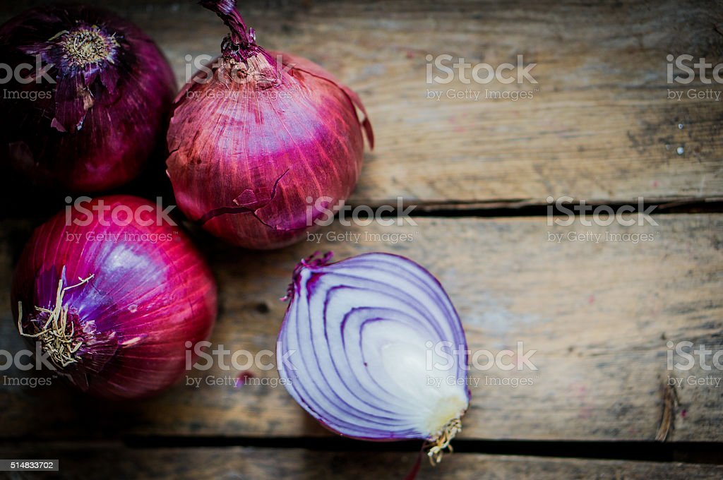 Red onions on rustic wooden background stock photo