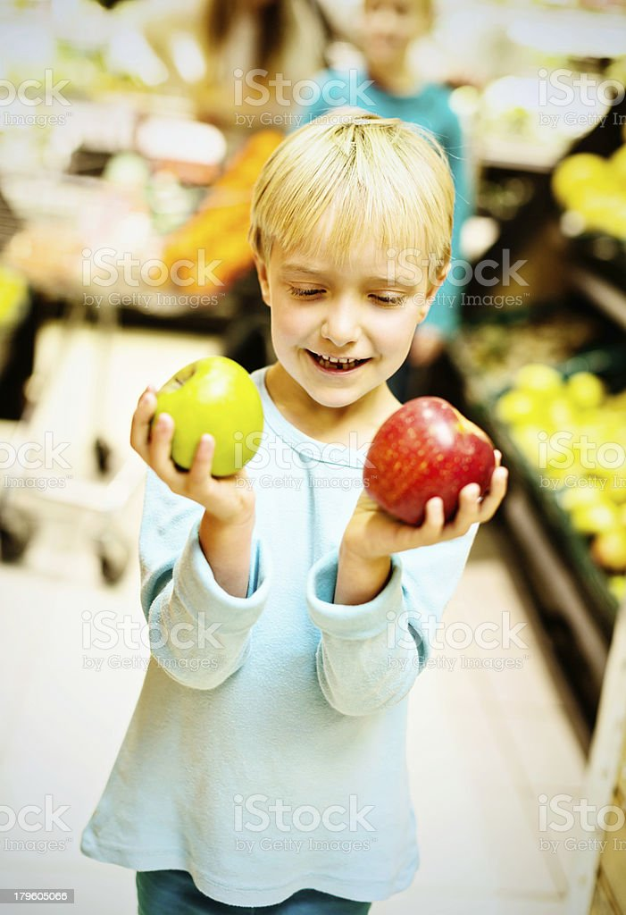 Red or green? Little girl in supermarket selecting apples royalty-free stock photo