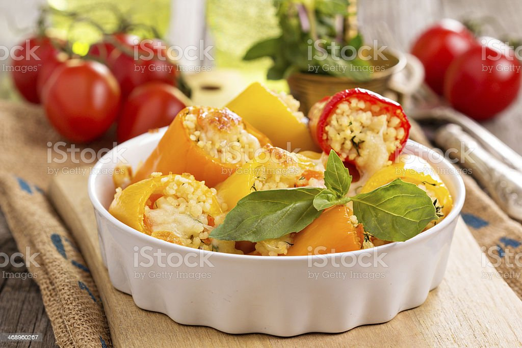 Red, orange and yellow stuffed peppers in a white dish stock photo